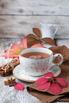 Cup of autumn tea on light  wooden background