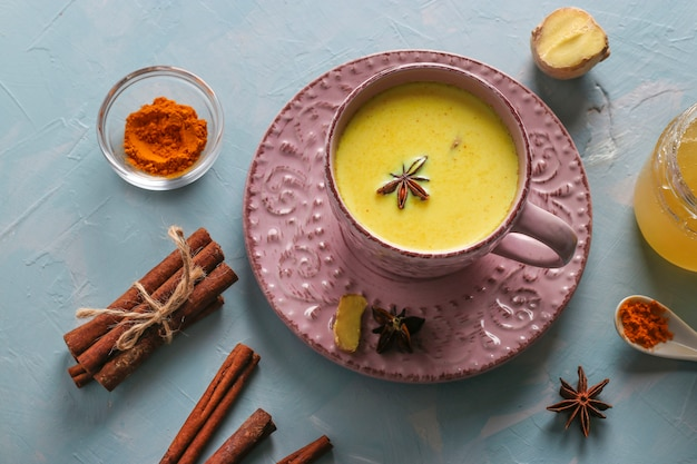 Cup of ayurvedic golden turmeric latte milk with curcuma powder, cinnamon, ginger and anise star on light blue surface, top view
