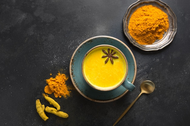 Cup of ayurvedic golden turmeric milk with curcuma powder and anise star on black. view from above.