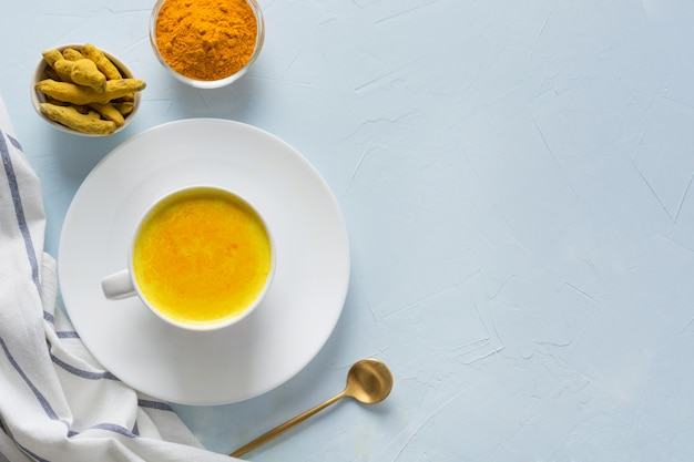 Cup of ayurvedic golden turmeric milk with honey on blue. copyspace or recipe. healthy drink for immunity. top view. natural food