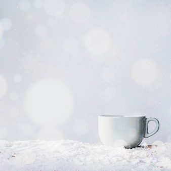 Cup on bank of snow and snowflakes