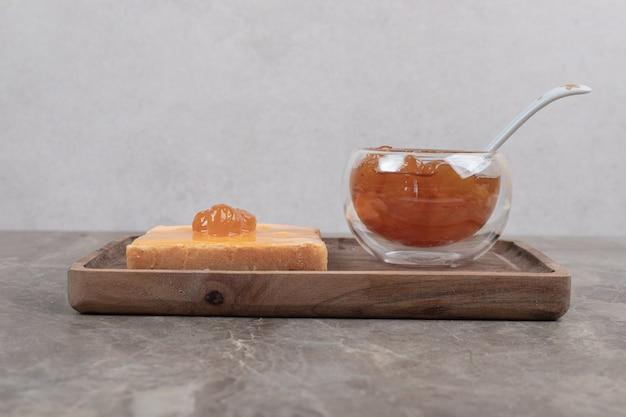 Tazza di marmellata di frutti di bosco con cucchiaio e pane tostato sul piatto di legno. foto di alta qualità