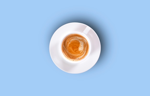 Cup of black coffee on a blue background. top view. hard shadow.