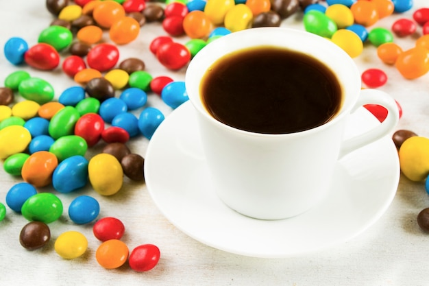 Cup of black coffee and chocolate candy