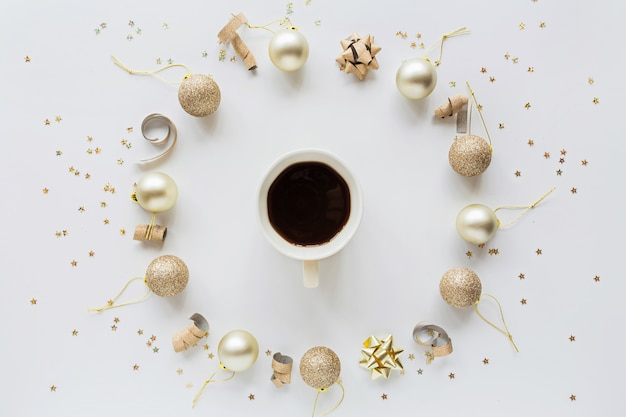 Cup of black coffee and christmas balls on white