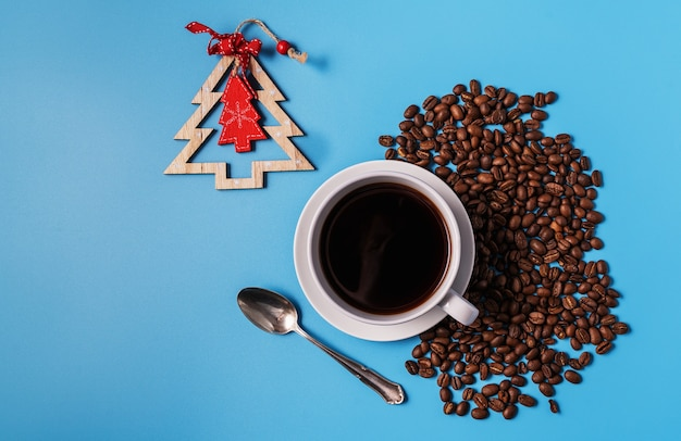 Cup of black coffee and coffee beans on blue background, copy space for text. christmas concept.