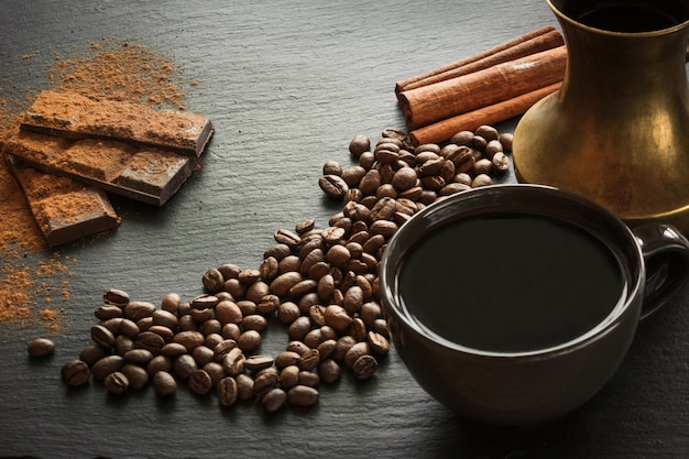 Cup of black coffee, coffee beans, chocolate bar, cinnamon and old copper cezve on black slate