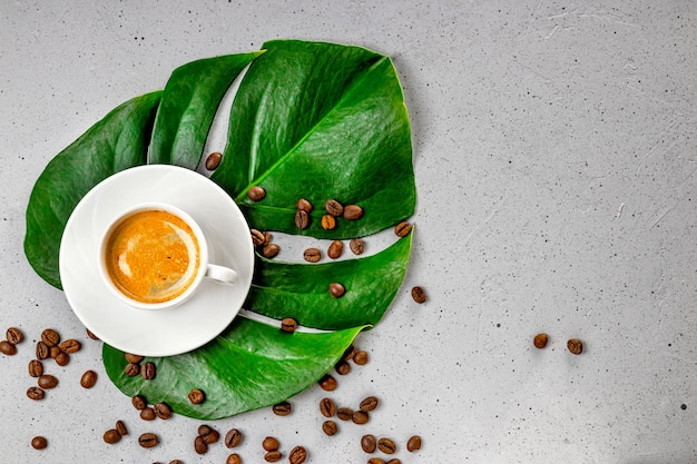 Cup of black coffee and coffee beans on monstera leaf and gray concrete background top view.