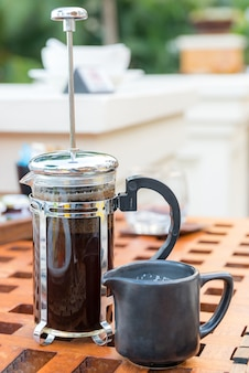 Cup of black coffee and french press on table at restaurant