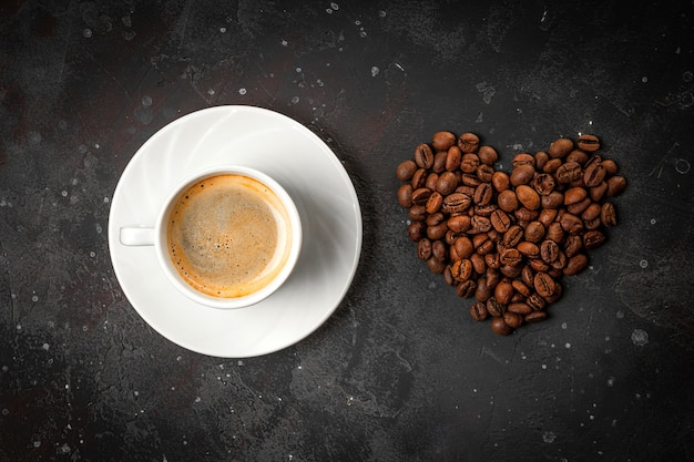 A cup of black coffee and heart shaped coffee beans on dark gray background