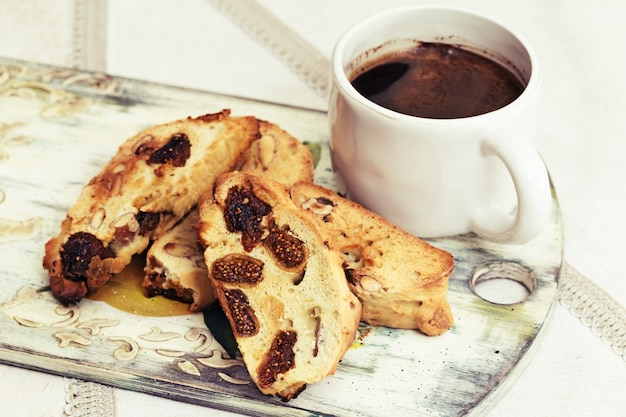 Cup of black coffee and homemade cookies biscotti on linen tablecloth.