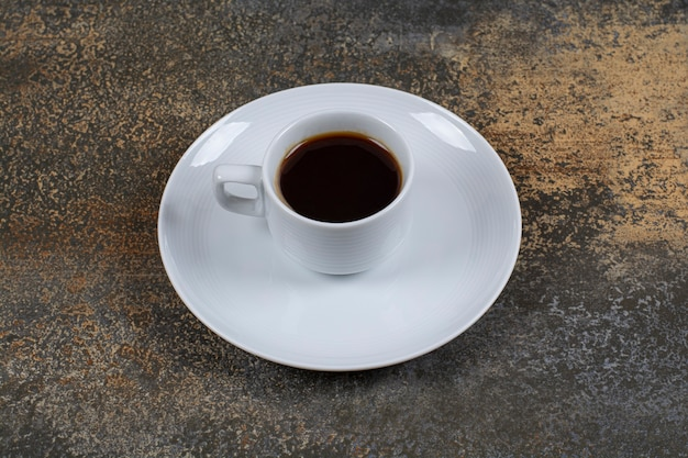 Cup of black coffee on marble surface.