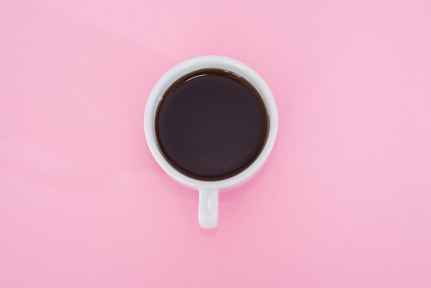Cup of black coffee on a pink background. view from above.