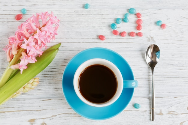 Cup of black coffee and pink flower