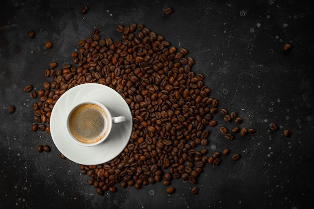 Cup of black coffee and roasted coffee beans on dark gray background top view, free space for text.