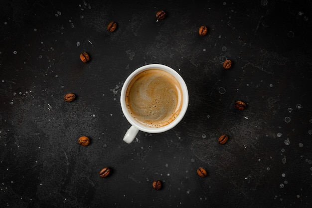 Cup of black coffee and roasted coffee beans on dark gray background top view