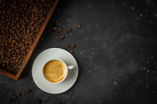 Cup of black coffee and roasted coffee beans in a wooden box on a dark gray background
