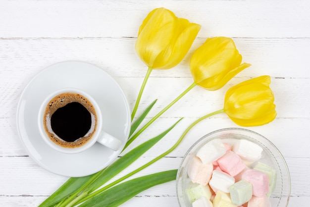 Cup of black coffee on a saucer, a bouquet of yellow tulips and marshmallows