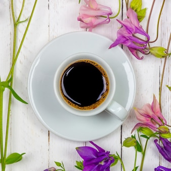 A cup of black coffee on a saucer and flowers on a white table