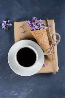 Cup of black coffee, waffle cone with purple lilac on blue stone concrete table background.