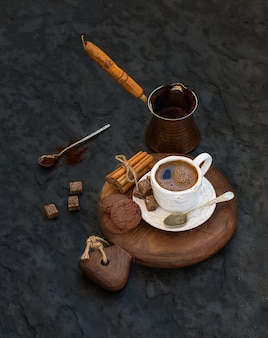 Cup of black coffee with chocolate biscuits, cinnamon sticks and cane sugar cubes on rustic wooden board over dark stone wall.