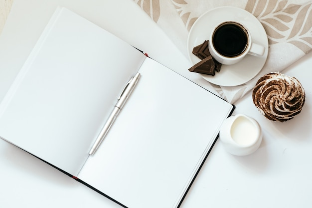 Cup of a black coffee with chocolates and cupcakes and an open notebook on white backgruond