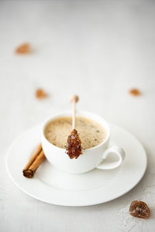A cup of black coffee with cinnamon and caramelized sugar on a stick, on a white table