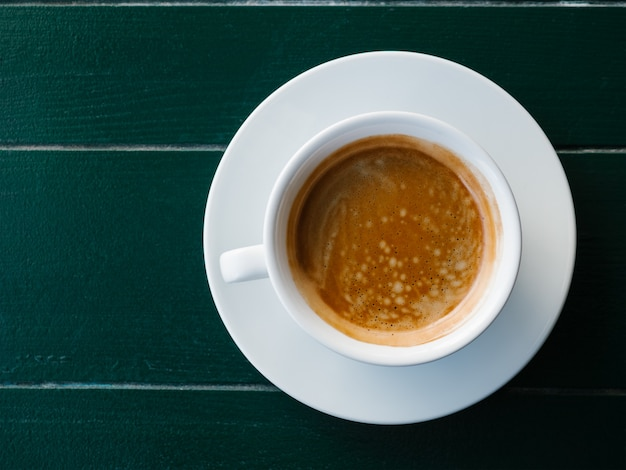 A cup of black coffee with foam on a emerald wooden background espresso or americanoe