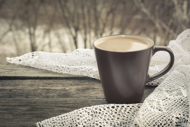 Cup of black coffee with milk  in front of the window and a lace on the wood