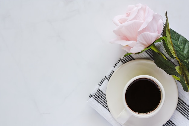 Cup of black coffee with saucer and sweet pink rose on napery