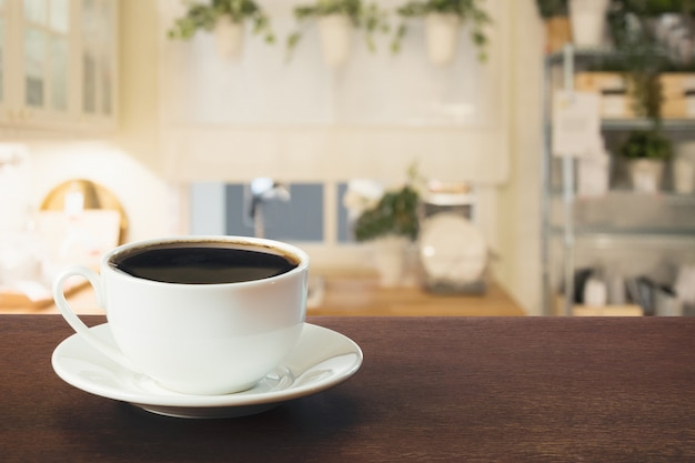 Cup of black coffee on wooden tabletop in blurred modern kitchen or cafe. close up. indoor.