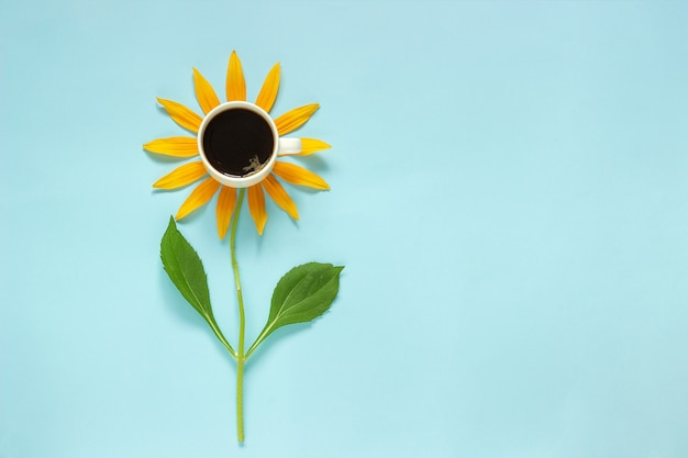 Cup of black coffee and yellow petals stalk flower shaped. concept good morning