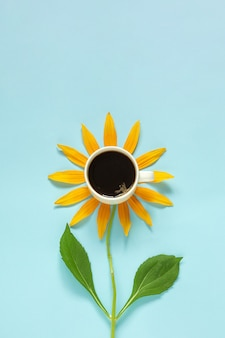 Cup of black coffee and yellow petals