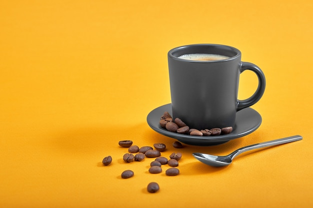 Cup of black coffee on a yellow