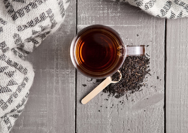 Cup of black healthy tea scarf and loose tea on wooden surface