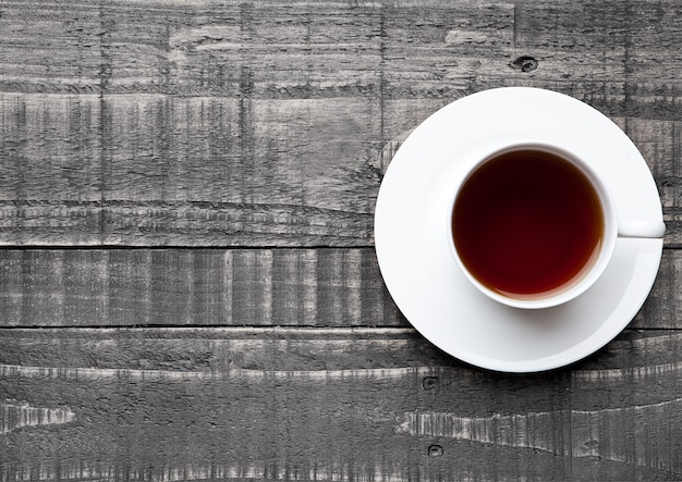 Cup of black healthy tea on wooden surface