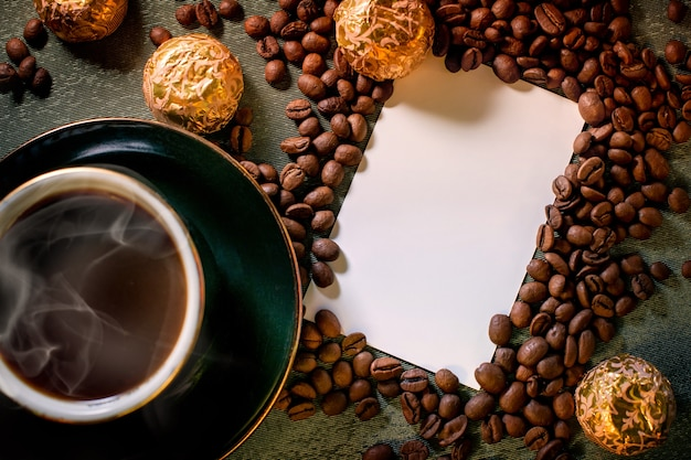 A cup of black hot aromatic coffee on the table, chocolates, coffee beans scattered around background