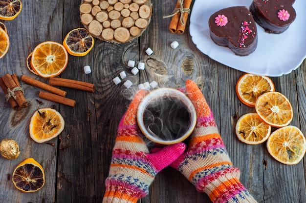 Cup of black hot coffee in her hands, wearing colorful winter gloves on hands