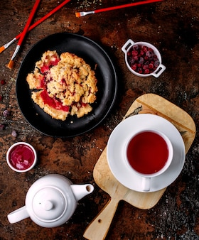 A cup of black tea and berry pie