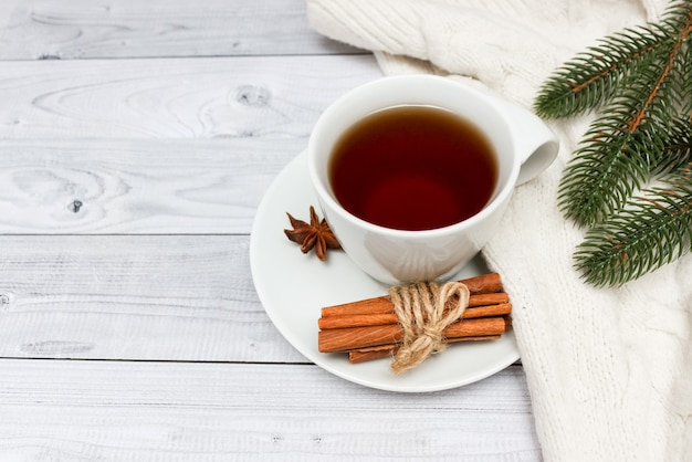 Cup of black tea covered with scarf. christmas tree in background. winter concept.