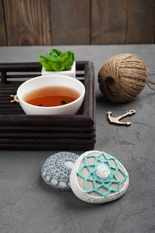 Cup of black tea and crocheted pebbles