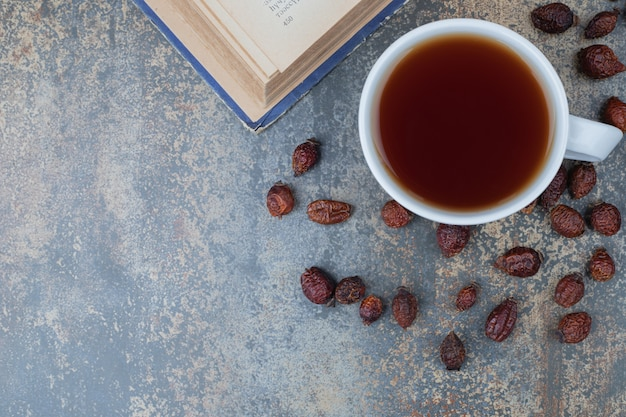 Cup of black tea and dried rose hip on marble background. high quality photo
