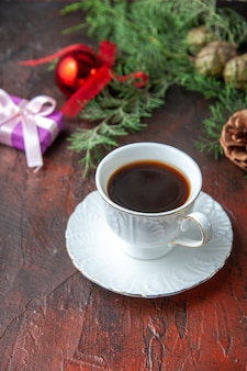 A cup of black tea fir branches decoration accessories and gift on dark background