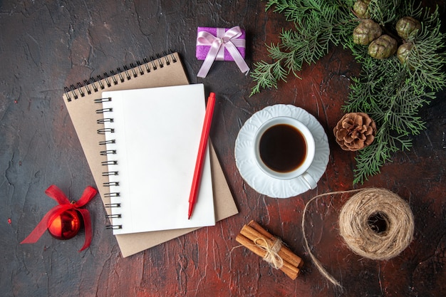A cup of black tea fir branches decoration accessories and gift and notebook with pen on dark background