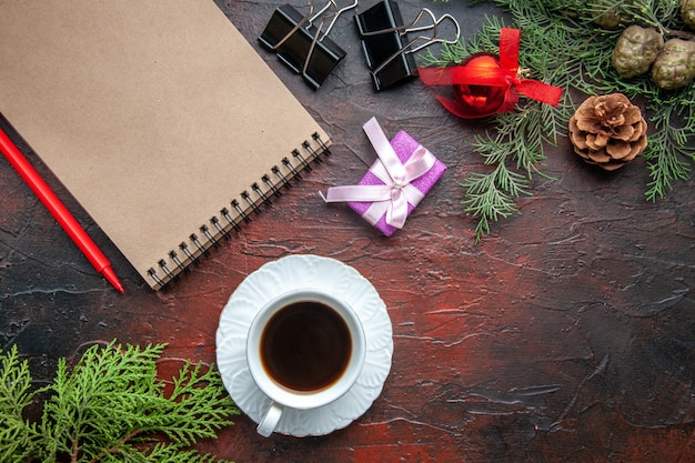 A cup of black tea fir branches decoration accessories and gift next to notebook with pen on dark background