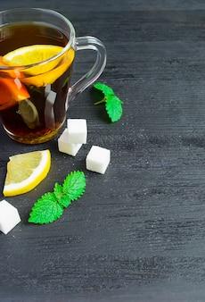 A cup of black tea, lemon slices, mint on wood