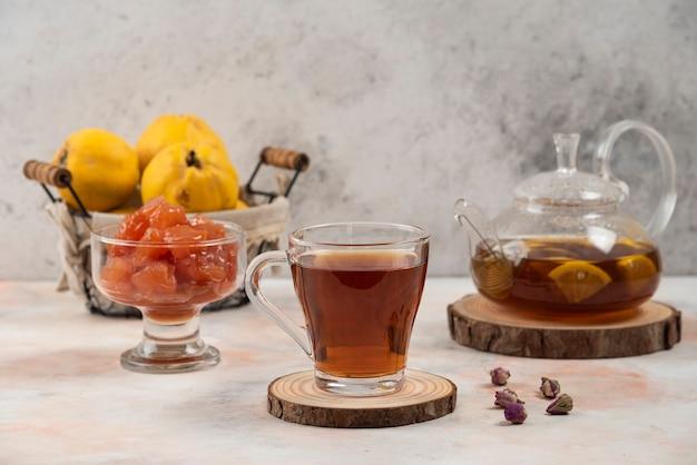 Tazza di tè nero, mele cotogne e marmellata sul tavolo di marmo.