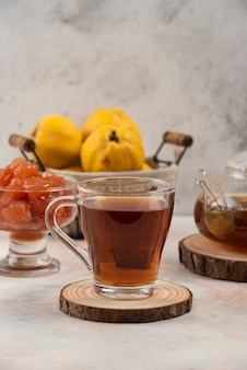 Cup of black tea, quince fruit and jam on marble table.