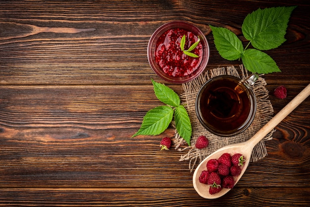 Cup of black tea and raspberry on dark wooden background