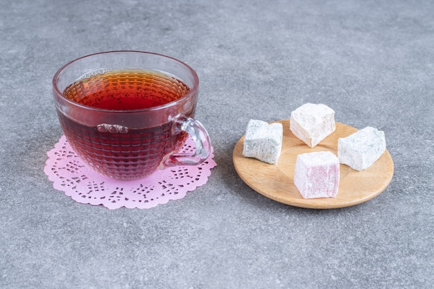 Cup of black tea and soft candies on marble surface